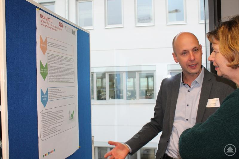 """Ein Teilnehmer des Hochschulzertifikats """"Systemische Prozessberatung im Betrieblichen Gesundheitsmanagement"""" präsentiert am BGM-Marktplatz sein Praxisprojekt."""