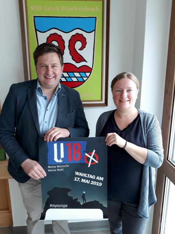 """KJR-Geschäftsführerin Anna Wagner beim Verteilen der Werbeplakate zur anstehenden """"U18-Wahl"""", hier Prackenbach mit Bürgermeister Andreas Eckl."""