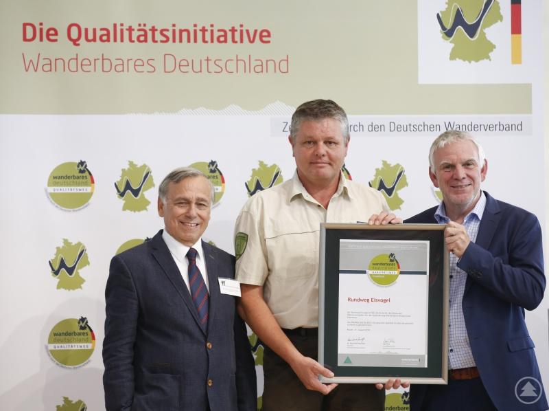 Ranger Roland Ertl (Mitte) erhielt von Dr. Hans-Ulrich Rauchfuß, Präsident des Deutschen Wanderverbandes (l.), und von Staatssekretär Jochen Flasbarth das Zertifikat für den Rundweg Eisvogel