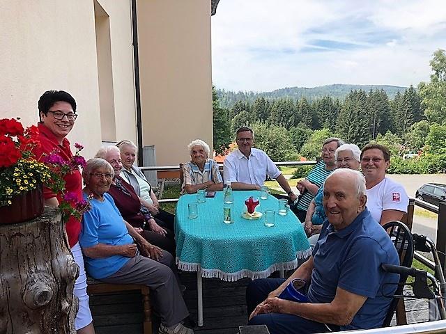 MdL Alexander Muthmann informiert sich über den Betreuungsdienst des Kreiscaritasverbandes Freyung-Grafenau. In Mauth genießen die Senioren den schönen Sommertag und schildern, was sie an dem Angebot schätzen. Links im Bild Leiterin Sonja Pangratz.