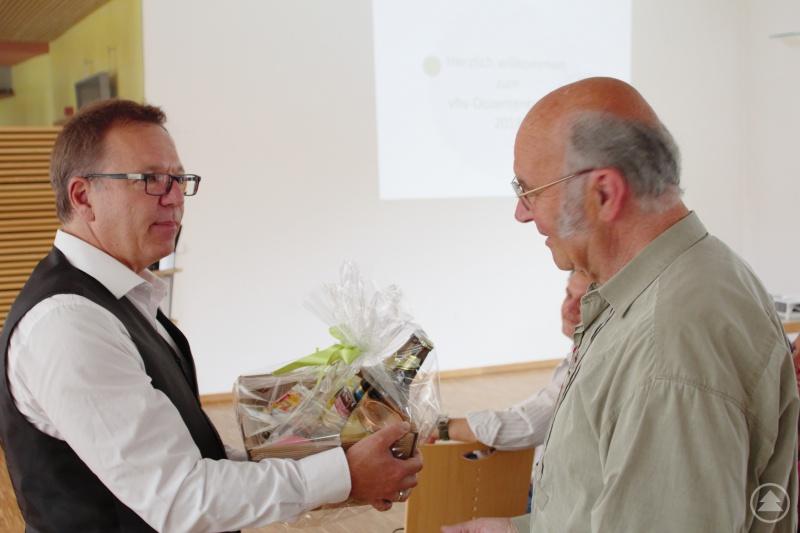 vhs-Geschäftsführer Michael Dietz (l.) verabschiedete den langjährigen vhs-Dozenten und Außenstellenleiter Norbert Schrüfer (r.) und überreichte ihm für seine Verdienste eine Ehrenurkunde und einen bayrisch-böhmischen Spezialitätenkorb.