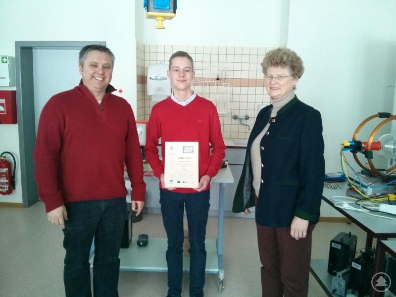 Der stolze Maximilian Sammer mit seiner Urkunde, die ihm gerade von seinem Physiklehrer Stefan Christoph und Schulleiterin Barbara Zethner überreicht worden war.