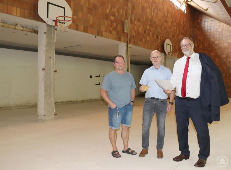 Oberbürgermeister Jürgen Dupper (von rechts) schaut sich mit Baureferent Wolfgang Seiderer und Hausmeister Hubert Ziegler die Muster für die Sanierung der Turnhalle der Sportgrundschule Grubweg an.