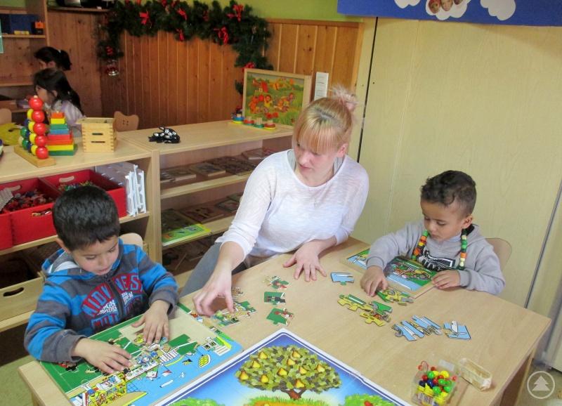 Die Kinder Mohamed und Almotasem zusammen mit Miriam Hirtreiter beim Puzzle bauen.