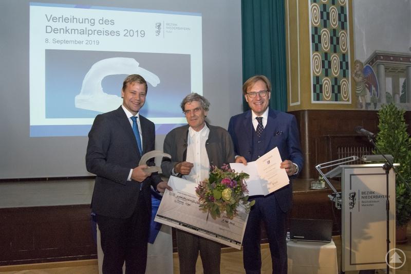 Bei der Verleihung des Denkmalpreises: Bezirkstagspräsident Dr. Olaf Heinrich (l.), Bezirkstagsvizepräsident Dr. Thomas Pröckl (r.) und der Preisträger Thomas Niggl.