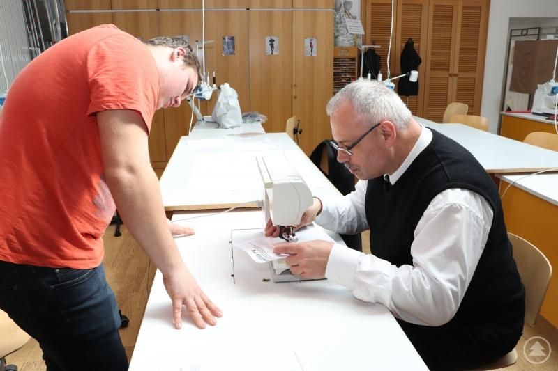 Generalvikar Dr. Klaus Metzl konzentriert beim Nähen. Kevin Klinginger schaut genau hin.