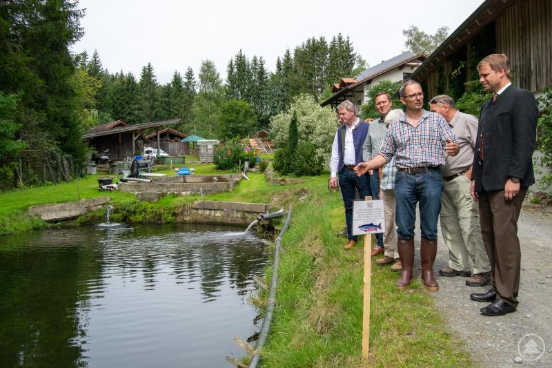 Thomas Flohr führte Bezirkstagspräsident Dr. Olaf Heinrich (re.) sowie die Bezirksräte Franz Schreyer und Josef Heisl (v.li.) durch seinen Fischzuchtbetrieb in Grünmühl.