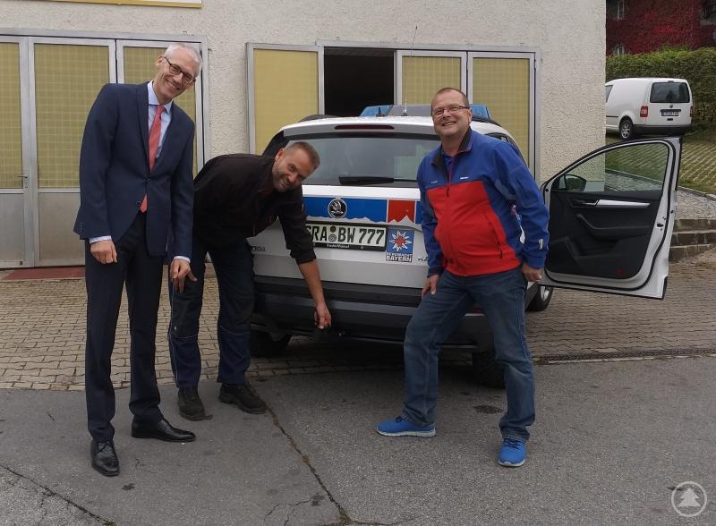Thomas Hatzinger zeigt dem Spender Notar Jörg Saumweber und Bereitschaftsleiter Harald Keller die neue Anhängerkupplung.