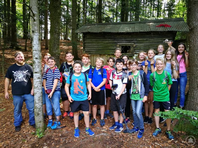 Die Kinder 6c hielten am Ende stolz einige ihre Funde hoch, die sie unter kundiger Anleitung von Sondengeher Michael Wagner (links) in einem Wald nahe Freyung ersondelt hatten.