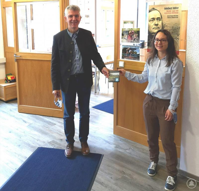 Bürgermeisterin Kristina Urmann (rechts) überreicht MdL Prof. Dr. Gerhard Waschler (links) eine Wanderkarte der Region um Neureichenau.