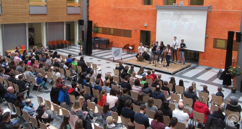 Gut gefüllt war die Aula des Gymnasiums bereits beim ersten Lied der Schulband; im Hintergrund lief eine Präsentation mit Fotos aus dem Schulleben am Gymnasium Freyung.