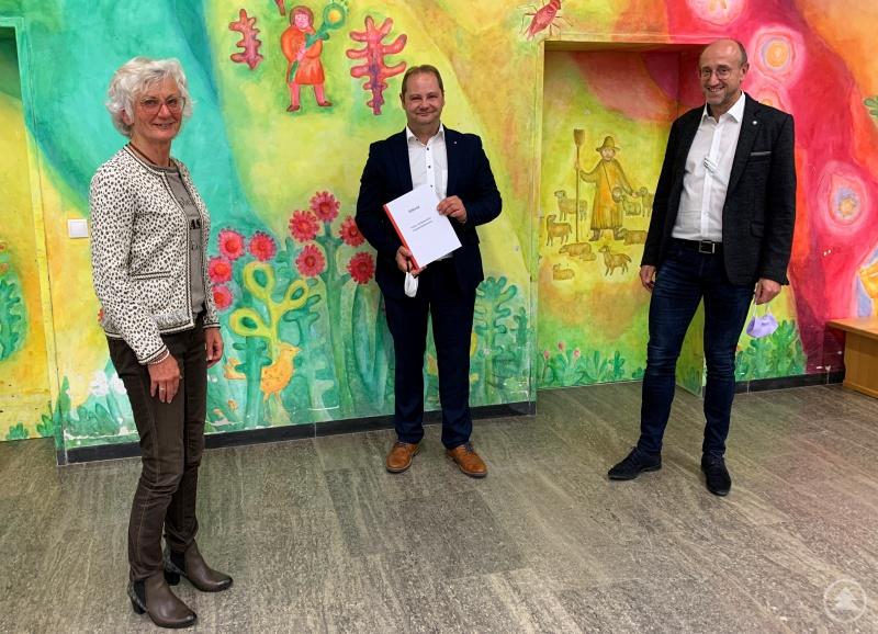 Aufsichtsratsvorsitzende Irene Hilz und ihr Stellvertreter Dr. Peter Robl übergeben dem neuen Aufsichtsrat Matthias Wendt (Mitte) die aktuelle Satzung des Kreis-Caritasverbandes Freyung-Grafenau e.V.