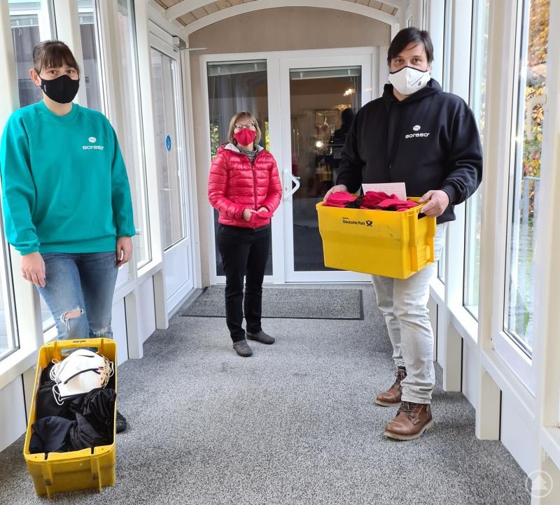 Eva Eder-Hackl (Mitte, Fachgebietsleitung Flexible Jugendhilfe) nimmt die Masken-Spende von Susanne Berndobler und Christian Hoffmann für den Caritasverband FRG in Empfang.