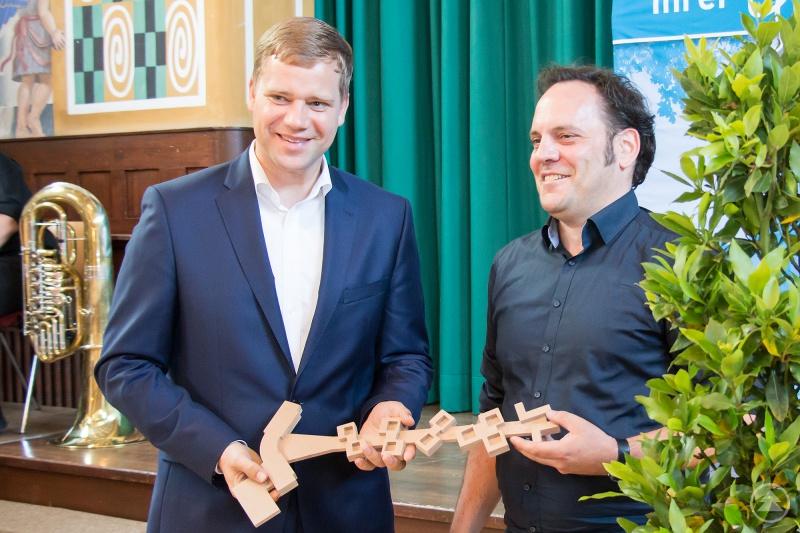 Architekt Jochen Eggert übergibt Bezirkstagspräsident Dr. Olaf Heinrich den symbolischen Schlüssel.