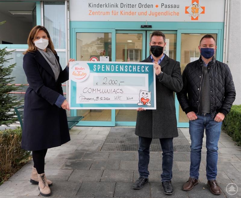 (v.l.) Dr. Maria Diekmann, Stiftungsvorstandsvorsitzende der Stiftung Kinderlächeln, nimmt von Christian und Stefan Höchtl, den Geschäftsführern der Firma Communiacs, den Spendenscheck über 2.000 Euro entgegen.