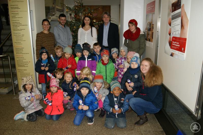 Dr. Klaus Stein, Vorsitzender der Geschäftsführung der Agentur für Arbeit Passau (mittig), Nina Schrank, Erzieherin (1. von rechts oben), Frau Theresa Bauer (vorne rechts), Sabine Bauernfeind (1. von links), Projektverantwortliche Arbeitsagentur Passau, zusammen mit den Kindern des Kindergartens St. Michael sowie den Auszubildenden der Arbeitsagentur