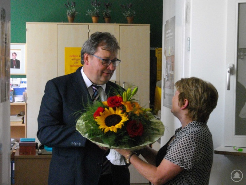 Blumen als ein kleines Zeichen für den großen Dienst in der Bahnhofsmission. Caritasvorstand Diakon Konrad Niederländer dankte Heidi Mayrhuber für 18 Jahre Sorge um Menschen in Not.