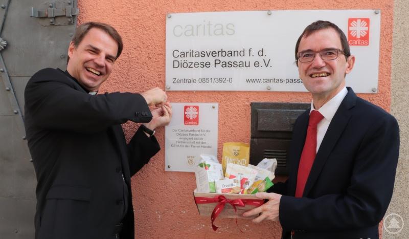 Die Partnerschaft der Caritas mit der The Fair Trade Company GEPA bezeugt jetzt ein Schild am Eingang. Bischof Dr. Stefan Oster hat es angebracht. Caritasvorstand Michael Endres überreichte GEPA-Produkte.