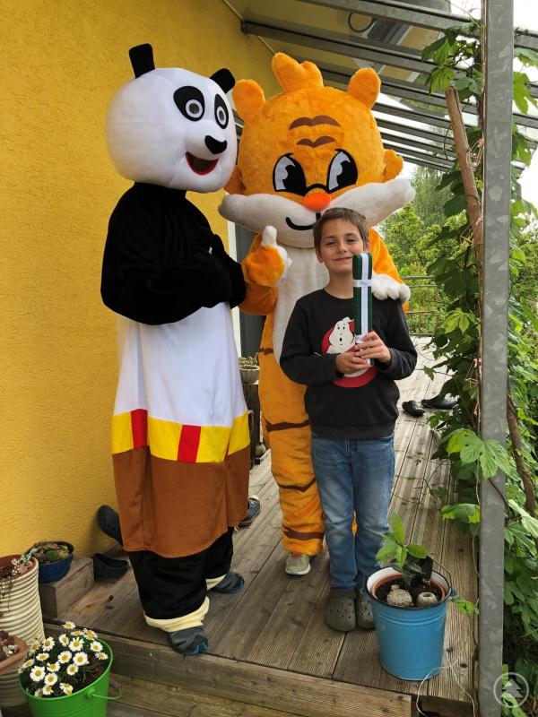 Leo erhält seinen Gürtel aus den Händen von Kungfu Panda und Karate Tiger.