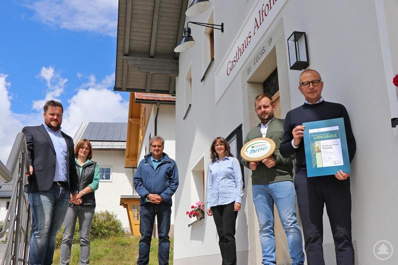 Das Nationalpark-Partner-Schild schon einmal vor die Eingangstür gehalten haben Inhaber Bernhard Fuchs (v.r.) und Geschäftsführer Thomas Dorner. Zur Mitgliedschaft im Verein gratulierten Katrin Wachter und Elke Ohland (2.v.l.) vom Nationalpark, Leiter Dr. Franz Leibl und Heiner Kilger (l.), dritter Bürgermeister von Mauth.